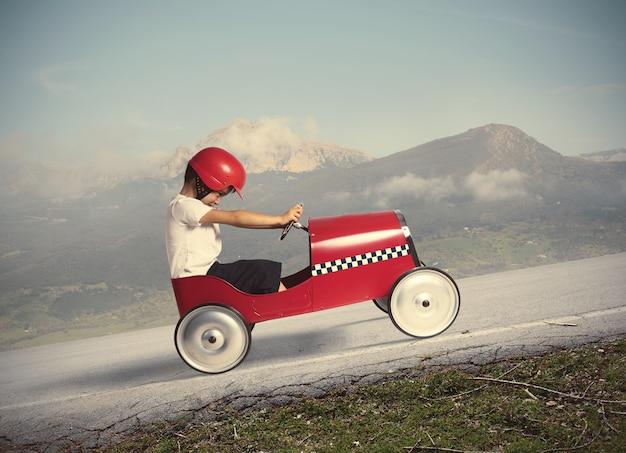 Kind besteigen einen berg mit einem kleinen spielzeugauto