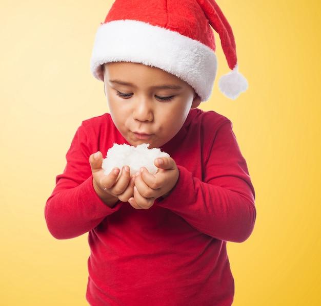 Kind bläst schnee mit einem sankt hut