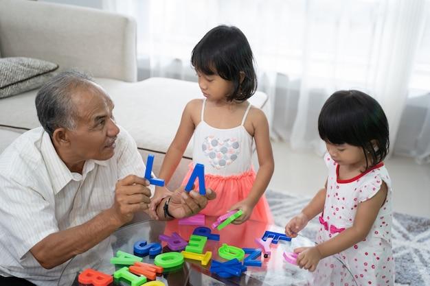 Kind, das alphabetbuchstaben mit opa lernt