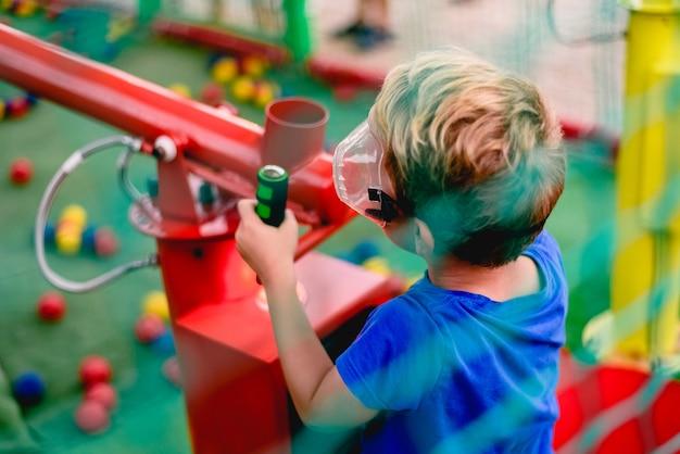 Kind, das an einem sommermarkt mit einer kanone von farbigen bällen komprimierter luft spielt.