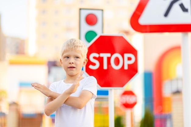 Kind, das an einem stoppschild steht und hände in einem kreuz hält
