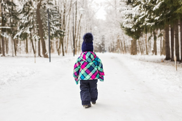 Kind, das an einem wintertag im wald weggeht.