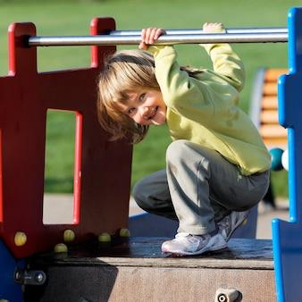 Kind, das auf buntem spielplatz in einem park spielt