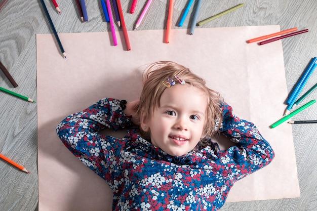 Kind, das auf dem boden auf papier liegt und die kamera nahe buntstiften betrachtet. kleines mädchen malt, zeichnet. draufsicht. kreativitätskonzept.