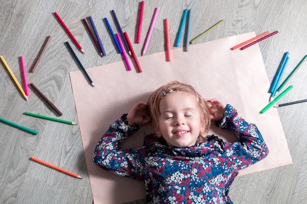 Kind, das auf dem boden auf papier mit geschlossenen augen nahe buntstiften liegt. kleines mädchen malt, zeichnet. draufsicht. kreativitätskonzept.