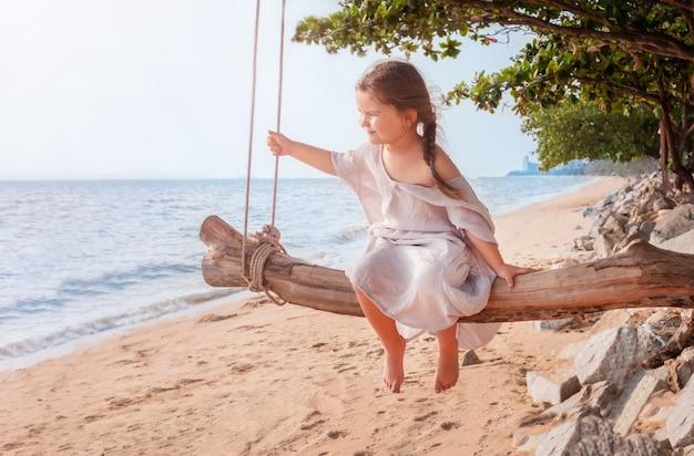 Kind, das auf einer hölzernen schaukel am strand am meer sitzt