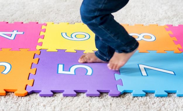 Kind, das auf einer nummerierten matte überspringt