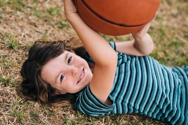 Kind, das auf gras liegt und ball hält