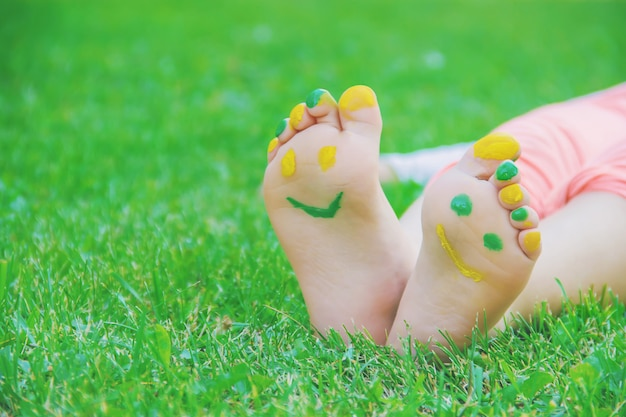 Kind, das auf grünem gras liegt kind, das draußen spaßpark im frühjahr hat.