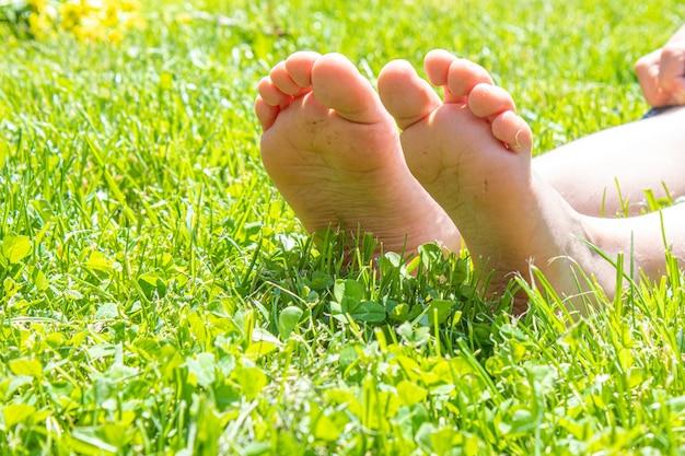 Kind, das auf grünem gras liegt. kind, das spaß im freien im frühlingspark hat. selektiver fokus. personen