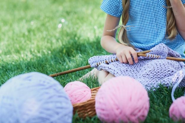 Kind, das auf grünem gras sitzt und pullover mit nadeln am sommertag strickt.