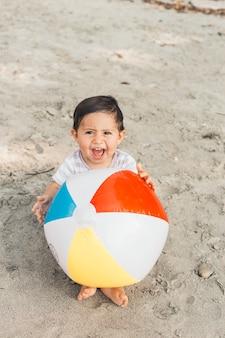 Kind, das auf sand mit aufblasbarer kugel sitzt