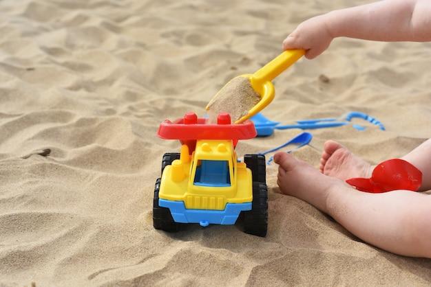 Kind, das auf sand nahe meer spielt.