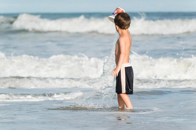 Kind, das auf seeküste im wasser spielt