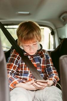 Kind, das auf smartphone im auto während einer straßenreise spielt