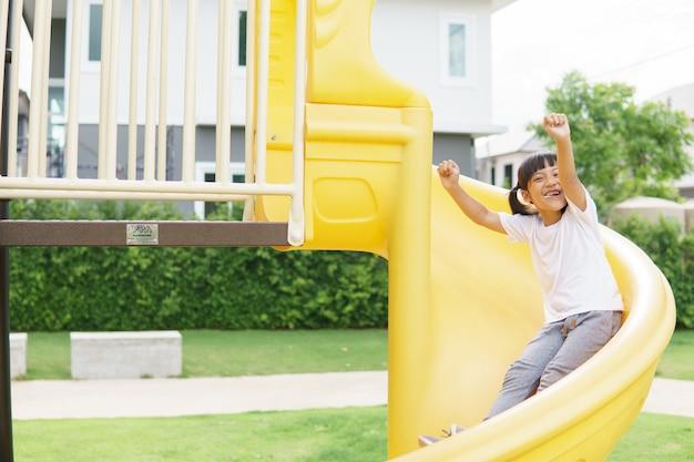 Kind, das auf spielplatz im freien spielt. kinder spielen auf dem schul- oder kindergartenhof.