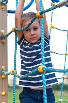 Kind, das auf spielplatz im freien spielt. kinder spielen auf der schule oder im kindergarten.