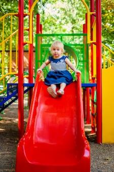 Kind, das auf spielplatz im freien spielt. kleines baby spielt auf schule oder kindergartenhof
