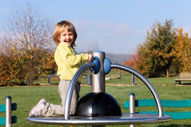 Kind, das auf spielplatz in einem park spielt