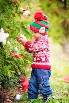 Kind, das auf weihnachten im holz wartet. porträt des kleinen jungen nahe weihnachtsbaum. baby, das kiefer verziert. winterferien und menschenkonzept. frohe weihnachten und schöne feiertage