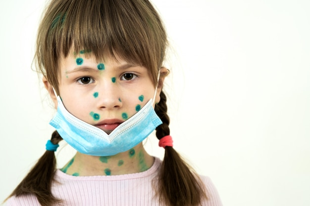 Kind, das blaue medizinische schutzmaske trägt, die mit windpocken-, masern- oder rötelnvirus mit hautausschlägen am körper krank ist.