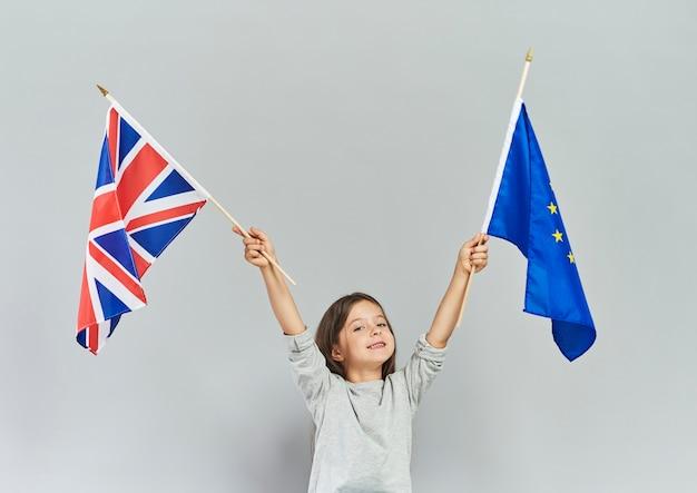 Kind, das britische flagge und flagge der europäischen union schwenkt