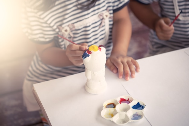 Kind, das das kleine mädchen malt, das spaß hat, auf stuckpuppe zu malen