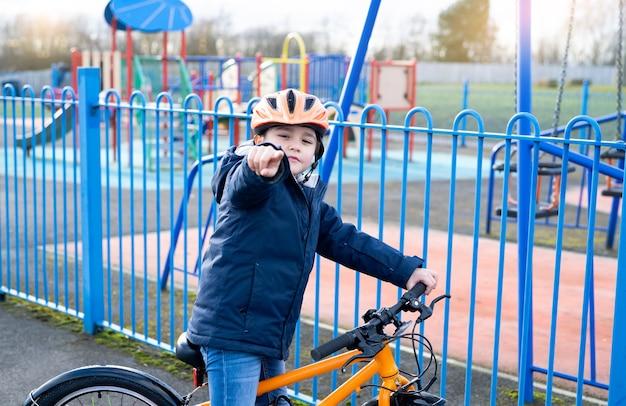 Kind, das den finger ausstößt, schulkind lernt, im park fahrrad zu fahren,