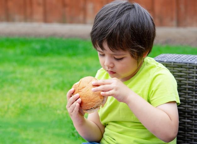 Kind, das den hamburger sitzt im garten isst