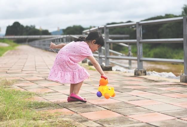 Kind, das den spaß spielt außerhalb des asiatischen kindermädchens glücklich mit spielwaren am internationalen tag der kinder des parks hat