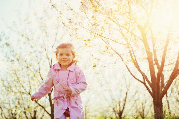 Kind, das draußen blüht bäume.