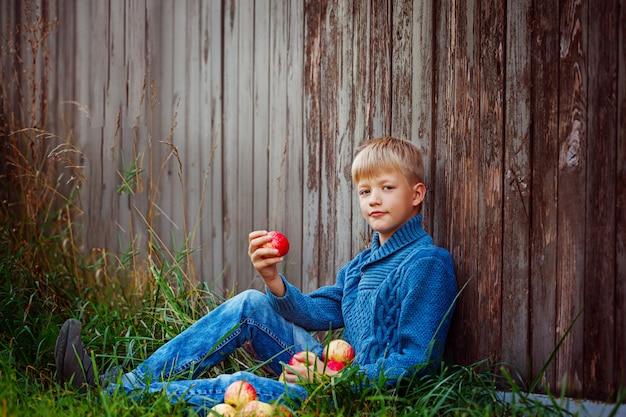 Kind, das draußen einen roten apfel im garten isst