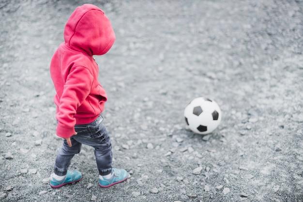 Kind, das draußen mit fußball spielt