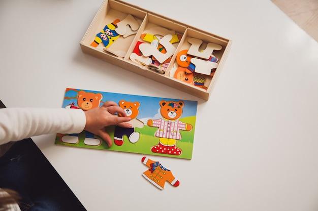 Kind, das ein brettspiel am weißen tisch spielt. frühe entwicklung eines kinderkonzepts.