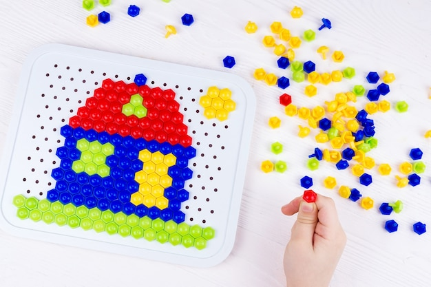 Kind, das ein mosaikhaus errichtet
