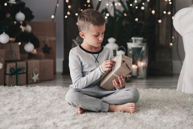 Kind, das ein weihnachtsgeschenk öffnet
