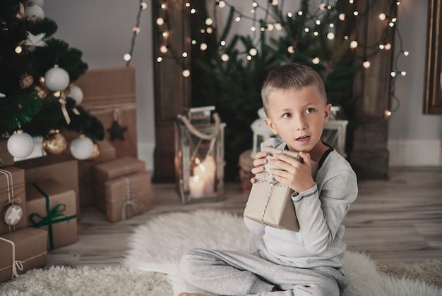 Kind, das ein weihnachtsgeschenk umarmt