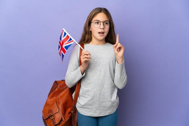 Kind, das eine britische flagge über isoliertem hintergrund hält, der eine idee denkt, die den finger nach oben zeigt