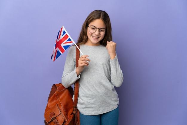 Kind, das eine britische flagge über isoliertem hintergrund hält, der einen sieg feiert