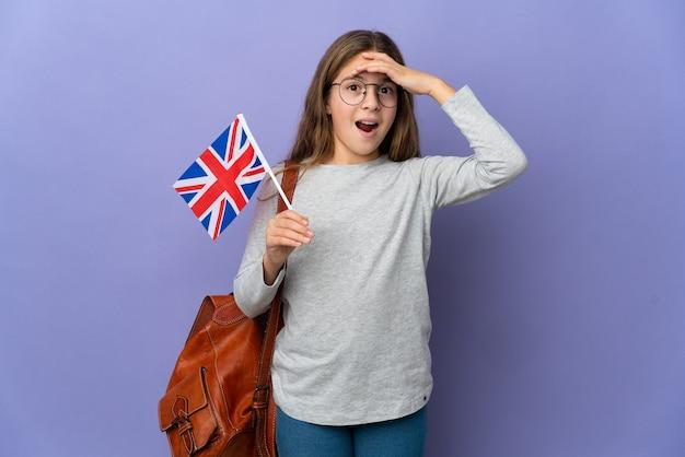 Kind, das eine britische flagge über isoliertem hintergrund hält und überraschungsgeste macht, während es zur seite schaut