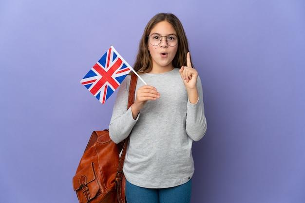Kind, das eine flagge des vereinigten königreichs über isoliertem hintergrund hält und beabsichtigt, die lösung zu realisieren, während es einen finger hochhebt