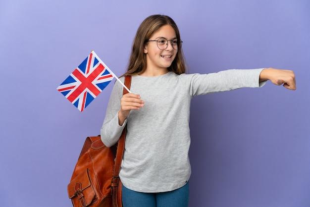 Kind, das eine flagge des vereinigten königreichs über isoliertem hintergrund hält und eine geste mit dem daumen nach oben gibt