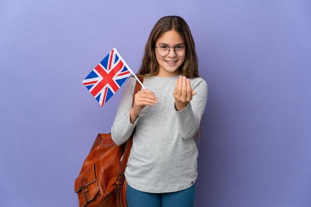 Kind, das eine flagge des vereinigten königreichs über isoliertem hintergrund hält und einlädt, mit der hand zu kommen. schön, dass du gekommen bist