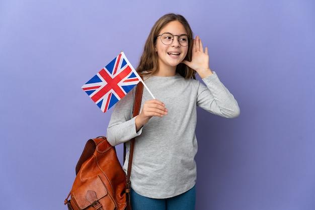 Kind, das eine flagge des vereinigten königreichs über isoliertem hintergrund hält und etwas hört, indem es die hand auf das ohr legt