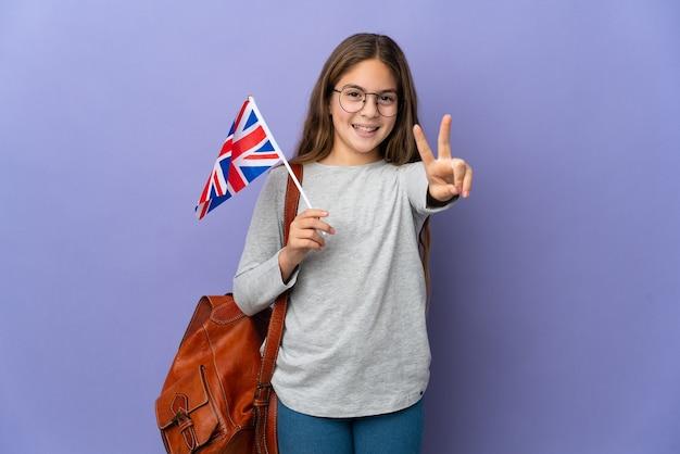 Kind, das eine flagge des vereinigten königreichs über isoliertem hintergrund hält und lächelt und victory-zeichen zeigt