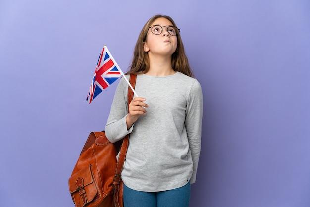 Kind, das eine flagge des vereinigten königreichs über isoliertem hintergrund hält und nach oben schaut