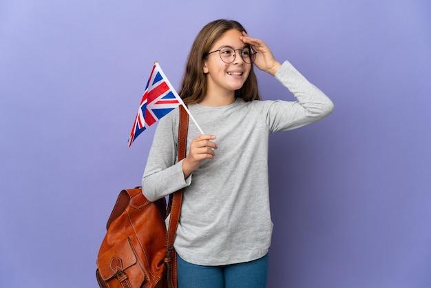 Kind, das eine flagge des vereinigten königreichs über isoliertem hintergrund hält und viel lächelt