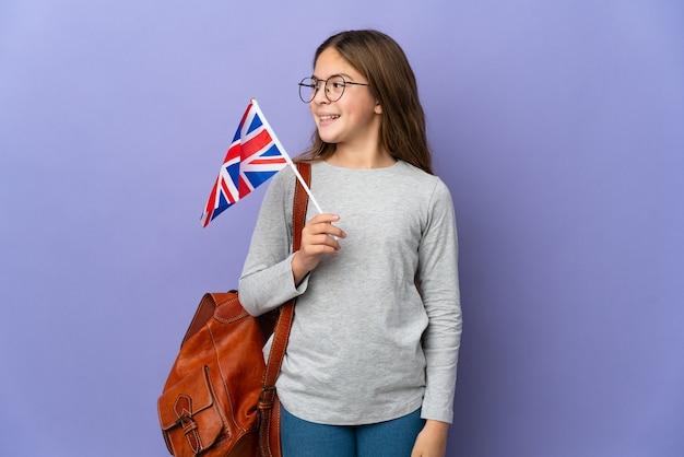Kind, das eine flagge des vereinigten königreichs über isoliertem hintergrund hält und zur seite schaut und lächelt