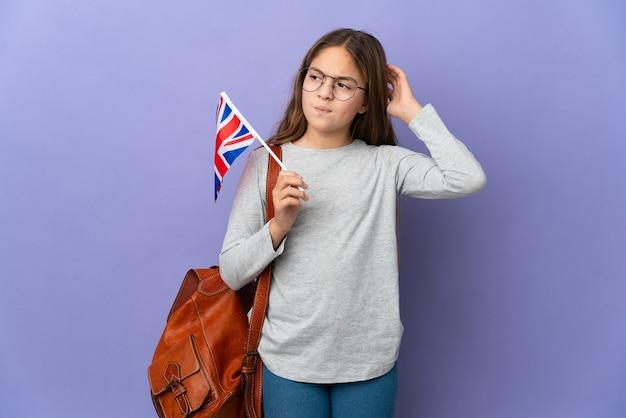 Kind, das eine flagge des vereinigten königreichs über isoliertem hintergrund hält und zweifel hat
