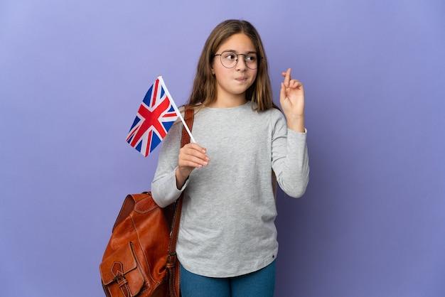 Kind, das eine flagge des vereinigten königreichs über isoliertem hintergrund mit gekreuzten fingern hält und das beste wünscht